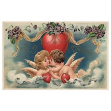 AMB Vintage Valentine postcard featuring two cupids kissing surrounded by hearts in the clouds