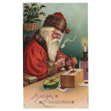 1908 Santa Claus working hard in his workshop marking packages Christmas Postcard