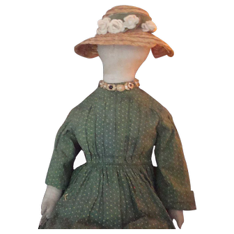Charming antique cloth doll withgreen calico dress and early straw bonnet 1870