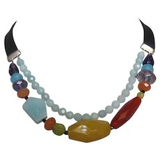 Two strand beaded necklace amethyst, carnelian, aquamarine, calcite, peridot stones on leather choker fitted to neck romantic contemporary jewelry design