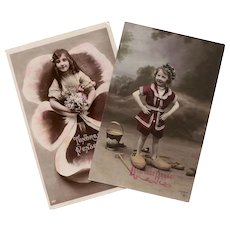 Two Antique French Postcards Sailor Suit Girl in Wooden Shoes and Edwardian Girl with Flowers
