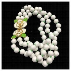 1973 MIMI D N White Double Strand Beaded Necklace with Green and White Enamel Flower Clasp
