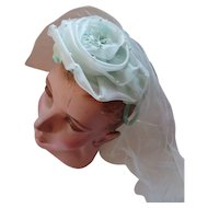 Confection of a Whimsy Hat in Mint Green Organdy Rose on Velvet Platform