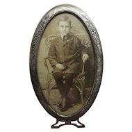 Early Framed Sepia Photo of Young Boy in Oval Stamped Metal Frame