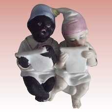 One Black  One White Bisque Baby On A Potty Singing