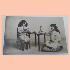 1910 Postcard with Girls Tea Party with Two Peg Wood Dolls