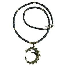 Brass Dragon Pendant on Necklace of Dark Grey Tube Beads
