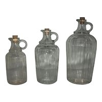 Three handled corked bottles in sizes