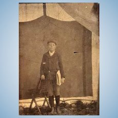 Tintype photo of Newsboy carrying Harper's Weekly