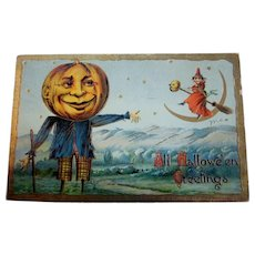 This is a vintage Halloween postcard with a jack o lantern scarecrow and a witch