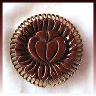 Carved brown bakelite and metal framed brooch