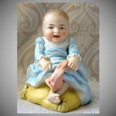 Humorous German Bisque Piano Baby Pulling off Her Sock