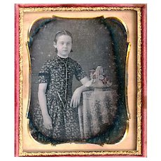 Hand-coloured Daguerreotype of a Girl with Gold Guard Chain & Pencil with Floral Basket on Table
