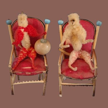 ** A Pair Of Chenille Figures In a Chair **