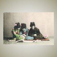 3 Japanese Ladies reading a Book. Tinted Vintage Postcard.