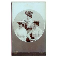 3 Ladies with fancy Hats on a Cabinet Photo