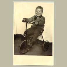 Happy boy on his tricycle. Vintage Photograph c. 1940