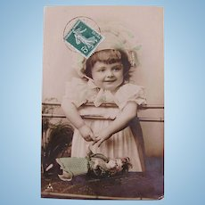 Tinted French Real Photo Postcard, Little Girl in Big Bonnet With Doll, Postmarked 1908