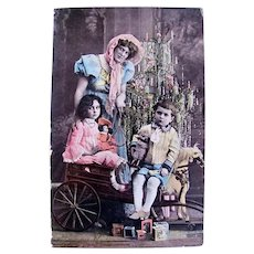 Tinted French Real Photo Postcard, Mother, Children, Doll and Toys & Tree, Postmarked 1906