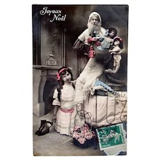 French Tinted Real Photo Postcard, Santa, 3 Dolls, Girl and Flowers, Circa 1910s