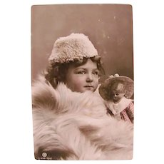 German Tinted Real Photo Postcard, Girl and Doll Wrapped in Fur, Circa 1910s