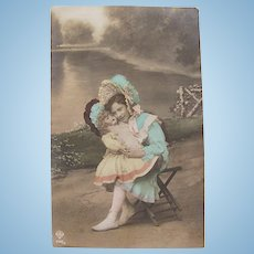 French Tinted Real Photo Easter Postcard, Girl and Doll Wearing Bonnets, Postmarked 1908