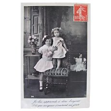 French Tinted Real Photo Postcard, 2 Children and Doll, Postmarked 1908