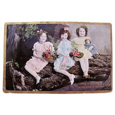 Hand Tinted Real Photo Postcard, 3 Little Girls, Flowers and Doll, Postmarked 1909