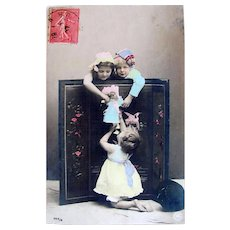 Hand Tinted French Real Photo Postcard, 3 Children Playing with a Doll, Postmarked 1907