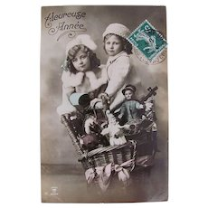 Hand Tinted French Real Photo Postcard, Children, Basket, Dolls and Toys, Heureuse Année, 1911