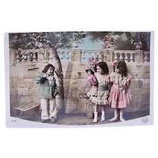 Tinted French Real Photo Postcard, Little Gardener, Girls and Doll, Dated 1911