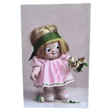 Glass-eyed Kewpie-Type Doll and Flowers, Tinted Real Photo Postcard, Circa 1920s