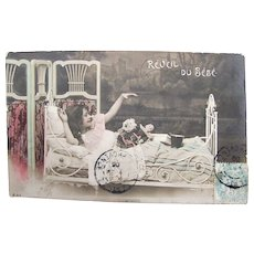 Tinted French Real Photo Postcard, Girl, Bed, Doll, The Baby Awakens, 1906