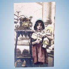 European Tinted Real Photo Postcard, Girl, Doll and Crèche, Circa 1910s