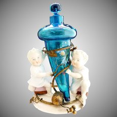 Antique blue glass scent bottle bisque children holder
