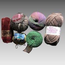 Six assorted skeins of knitting yarn in natural fibers