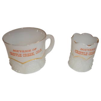 """A toothpick and a small cup both marked """"Souvenir of Cripple Creek, Colo.""""  Iridescent milk glass with gold colored trim."""