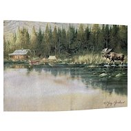 A Wall hanging picture of a Cabin on a lake with a moose.