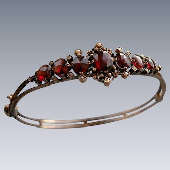 A 19th Century 8 ct Gold, Garnet and Seed Pearl Hinged Bracelet. Circa 1890.