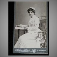 Antique Small German Cabinet Card of Beautifully Dressed Young Woman in Ornate Chair Reading a Book
