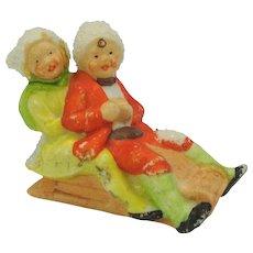 Vintage German bisque snowed cake decoration-boy and girl on sled