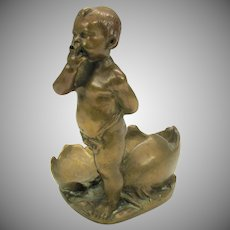 Antique bronze figure of a young child emerging from egg shells
