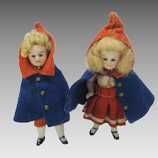 Pair antique German all bisque dolls in Red riding hood capes with glass eyes