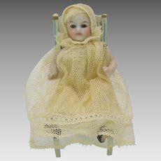 Antique German all bisque glass eyed dolls house doll in baby outfit for carriage