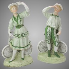 Pair antique German Heubach porcelain figures with bicycles