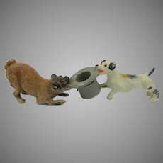 Antique cold painted metal figure Pug dog and Terrier tussling over a top hat