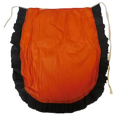 Crepe paper apron depicting orange and black Halloween colors 1922 – 1935