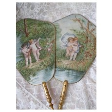 Pair delicious French hand painted face screens : cherubs : gilt wood handles : circa 1900