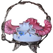 Brides Basket:  Cased Glass Brides Bowl Crimped and Folded Rim Dark Cranberry to Light Pink Interior Blue Enamel Floral Decor and White Exterior with Enameled Blue Floral and Pussy Willow Decor Sitting in James Tufts Footed and Cherry Inspired Basket