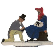Germany Metal Flat Man Puts on Woman's Ice Skates Christmas Winter Scene Figure